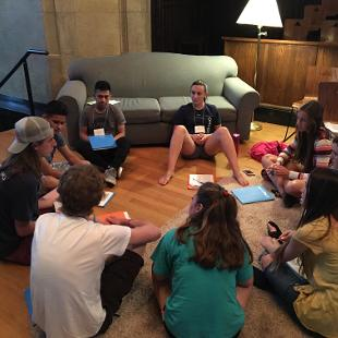 A small group of Awakening students sit with an intern.