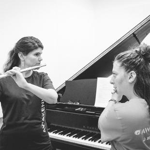 A female faculty member practices the flute with a female Awakening student