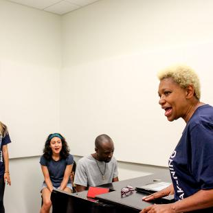 A female faculty member rehearses singing with a group of Awakening students