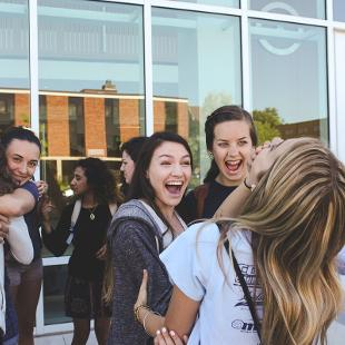 A group of Awakening students smiling and embracing in front of the Jack H. Miller Center