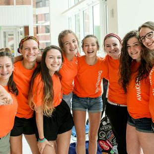 A group of female students smile for a picture in the Jack H. Miller Center