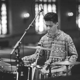 A male student playing the drums in Dimnent Chapel