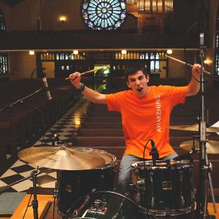 A male student playing the drums holding up his drumsticks in Dimnent Chapel