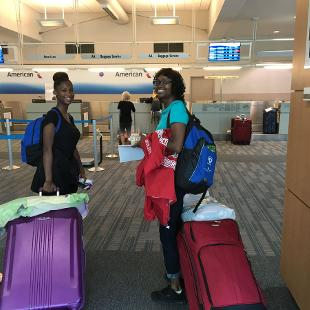 Two female students smile for a picture at the Gerald R. Ford International Airport