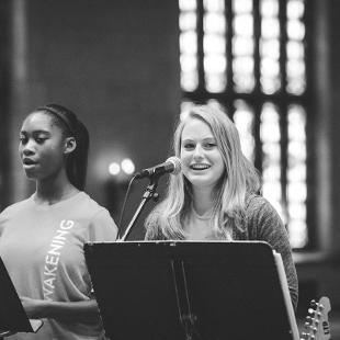 Two female students leading worship by singing in Dimnent Chapel