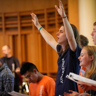 A male student praises while having his hands raised during a church service
