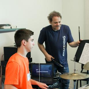 An Awakening faculty member assists a male student practice the drums