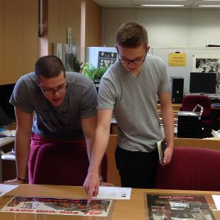 Jon and Cullen are looking at  poster on a table at the LOC