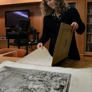 Anne in the rare book room opening a large book of maps