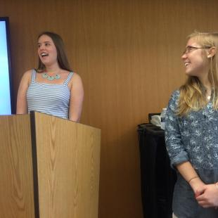 Maddy standing at a lectern with Hope looking on