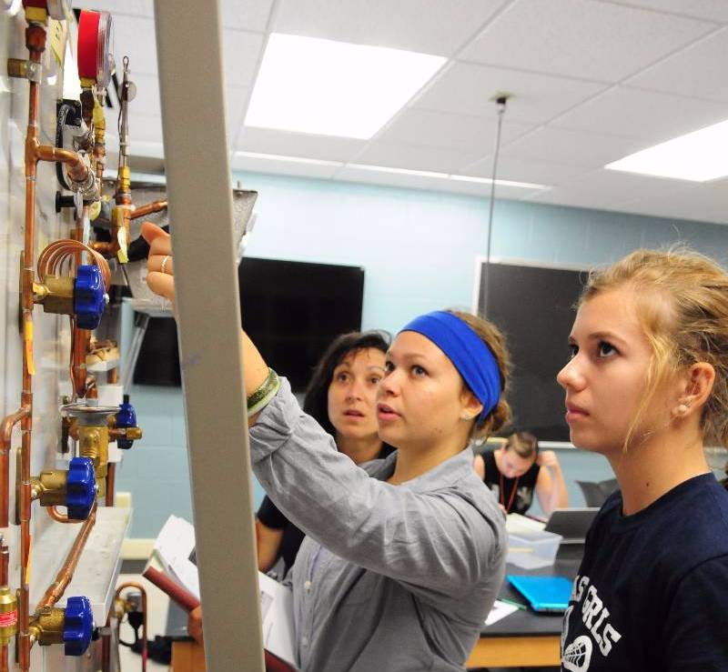 Students take measurements on a refrigeration laboratory demonstration in the introduction to engineering lab
