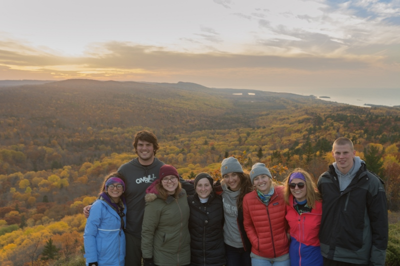 students on mountain with forest below in fall colors