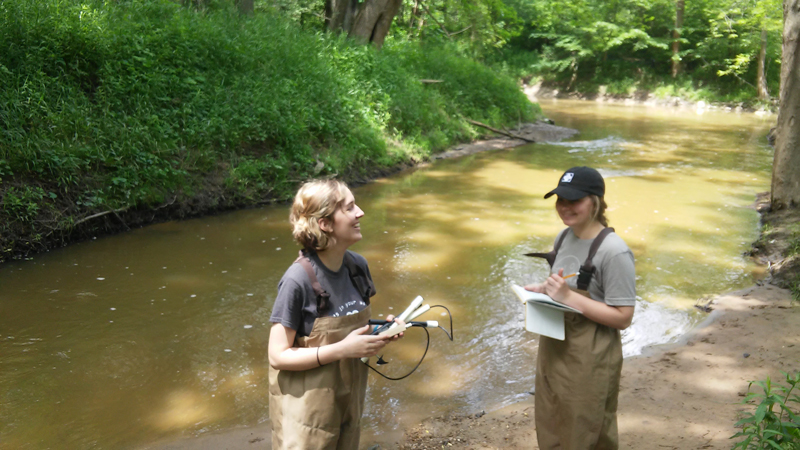 two students with stream flow measuring equipment in waders in a streambed