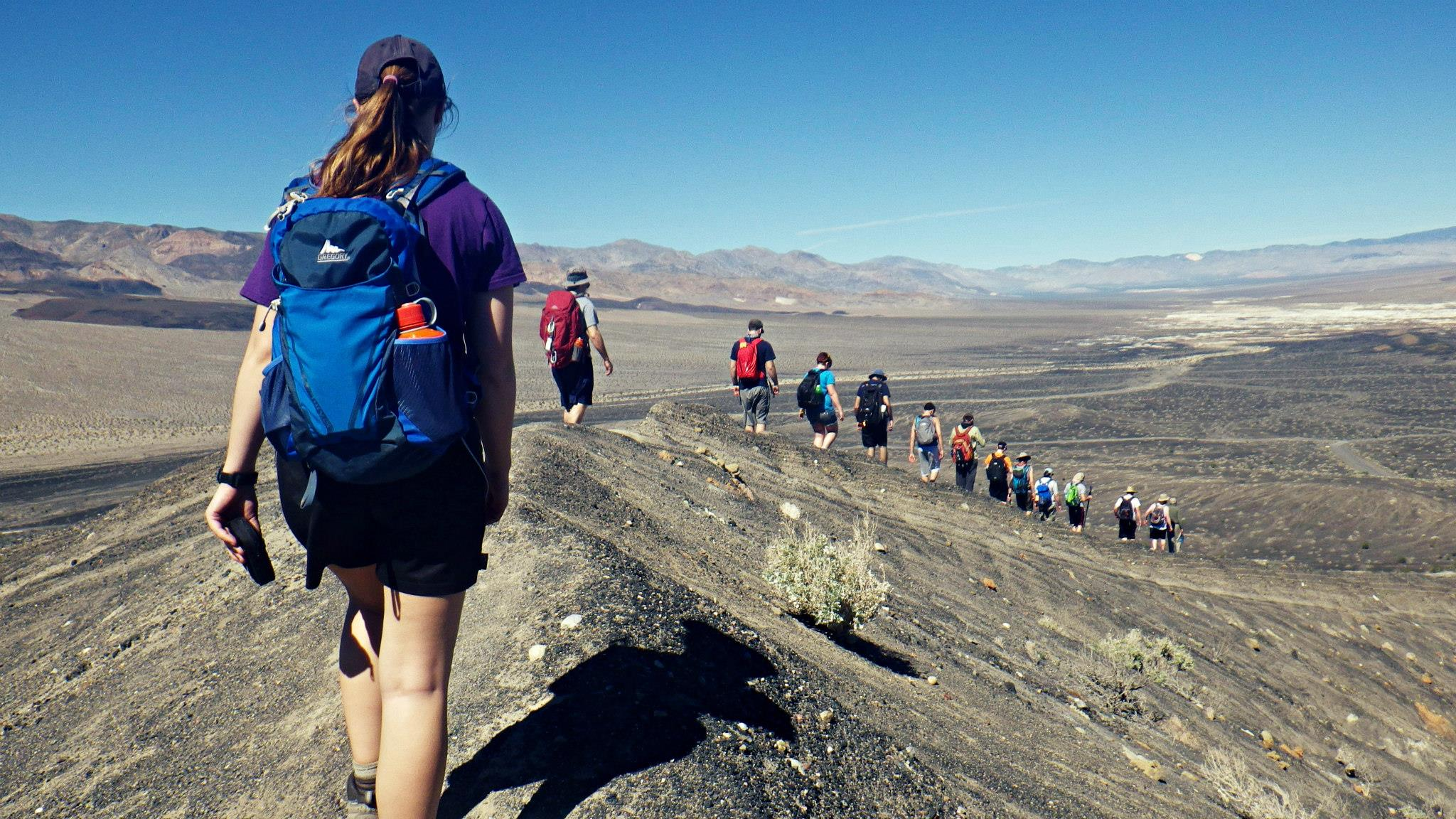 Students hiking along a ridge line down into Death Valley