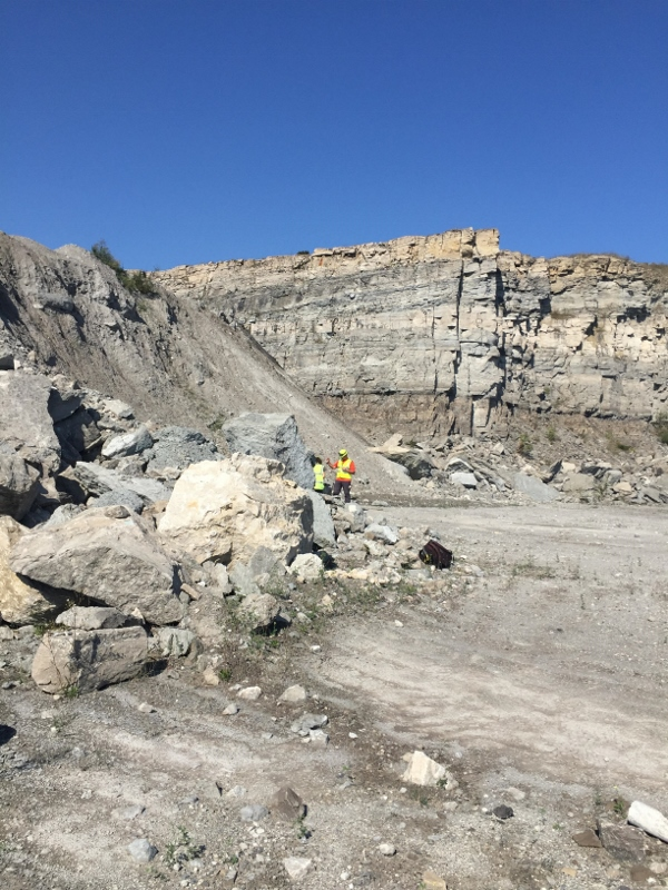 student examines a rock pile with a quarry highwall in the background
