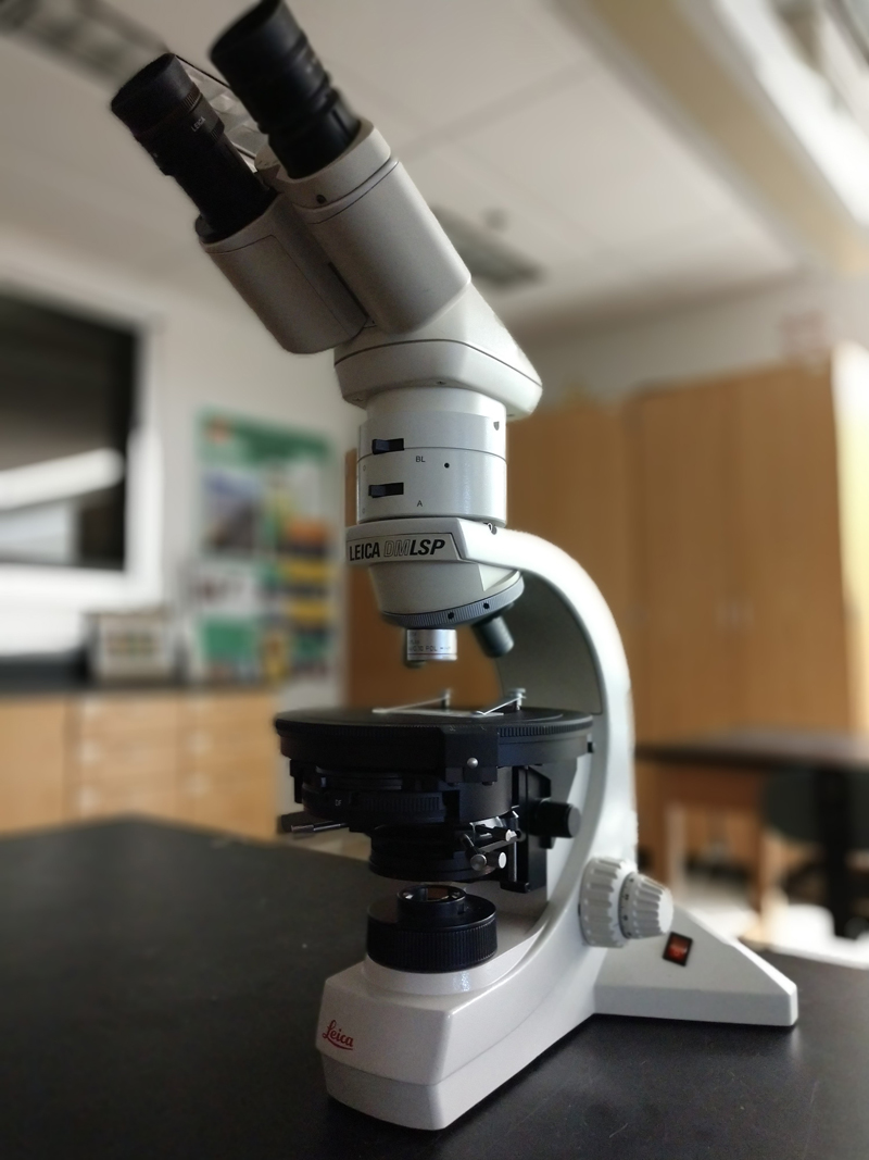 a binocular petrographic microscope on a lab table
