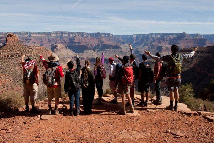 students with arms raised looking across the rim of the Grand Canyon