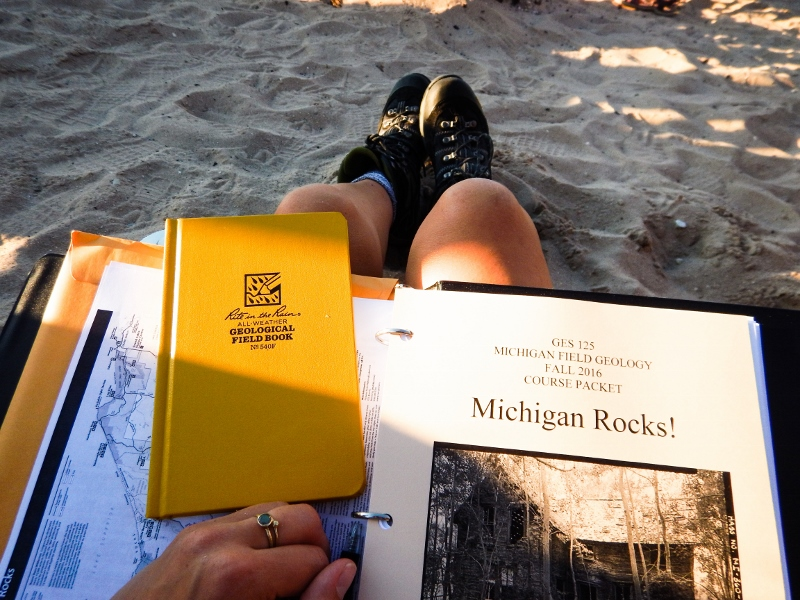 Michigan Fied Geology binder and field book on a student's lap with legs outstretched and hiking boots resting in beach sand