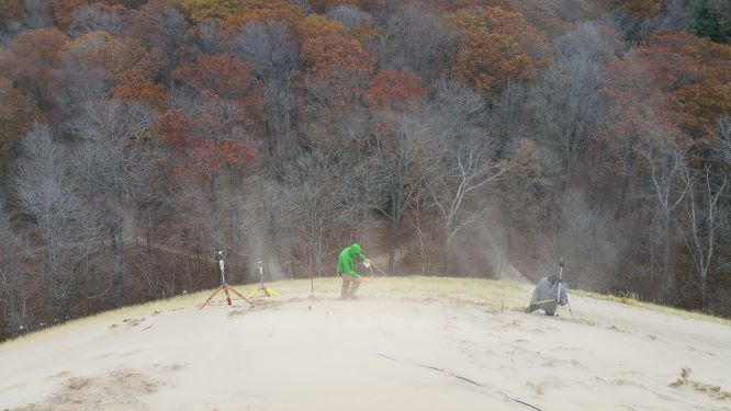 sand swirling around researchers on a dune slope high above the surrounding forest