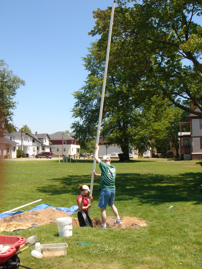 students guiding a 20 foot PVC pipe water well into a hole on a campus lawn