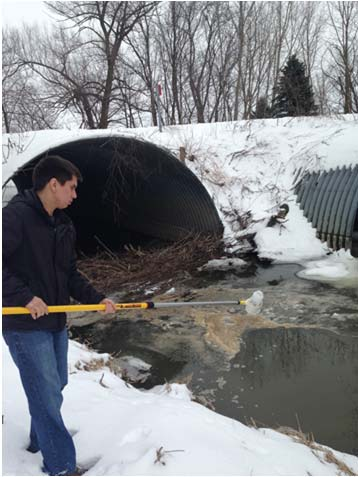 student holds a pole with a sampling bottle on the end over a stream by a snow-covered culvert