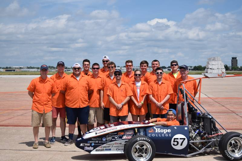 Members of the Hope College Formula Racing team pose with one of their cars at a 2018 competition.